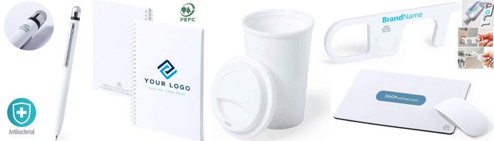 Varios productos antibacterianos que se pueden personalizar, un boli, una libreta, un vaso con tapa, un llavero anti-contacto y una alfombrilla y ratón para ordenador.